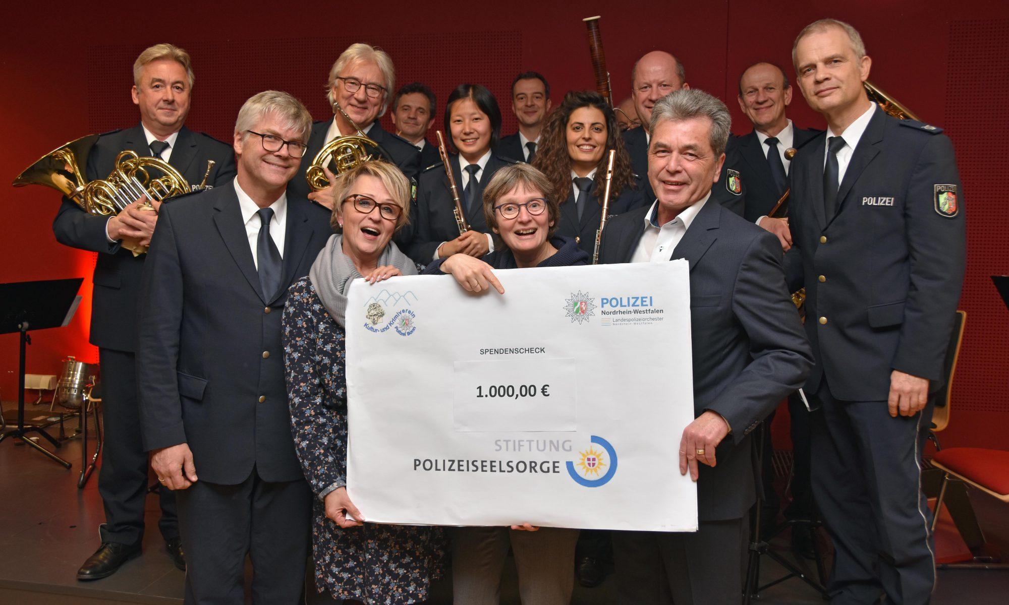 Bonns Leitender Polizeidirektor Helmut Pfau (re) und Christa Wennmann vom Kulturverein übergeben einen Spendenscheck an Polizeipfarrerin Claudia Heinemann